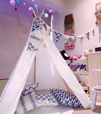 Blue and white teepee with bunting and cushions